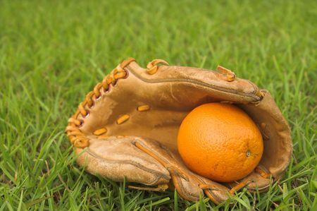 gant de baseball: Un d�licieux orange dans un gant de baseball.