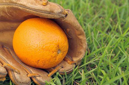 A delicious orange in a baseball glove. photo
