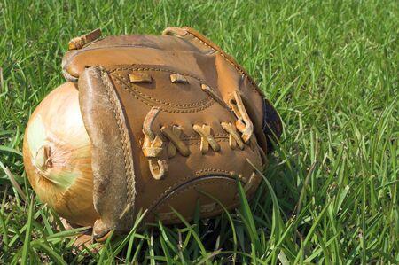 An onion resting in a baseball glove. photo