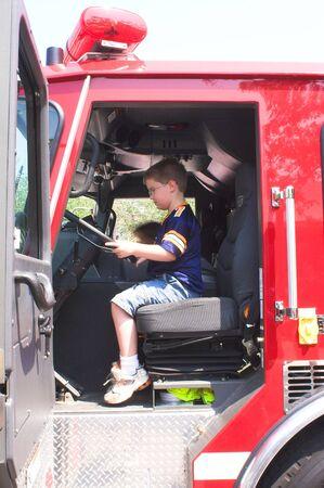 camion pompier: Un jeune gar�on assis dans un camion d'incendie.