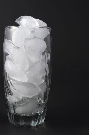 Ijs blokjes in een helder glas water.