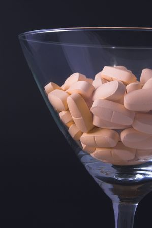 Pills in a martini glass - Drug abuse concept.