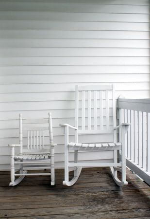antique chair: An adults and childs rocking chairs on a front porch.