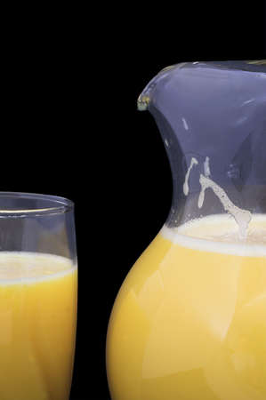 Orange juice in a drinking glass and a pitcher. photo