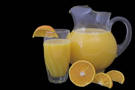 Orange juice in a pitcher and drinking glass with orange slices. photo
