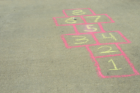 The sidewalk drawing game board of the childhood game of hopscotch.