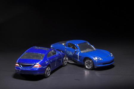 involving: Una macchina relitto che coinvolge due automobili giocattolo in miniatura.