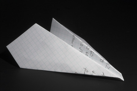 A paper airplane made out of a homework paper. Stock Photo