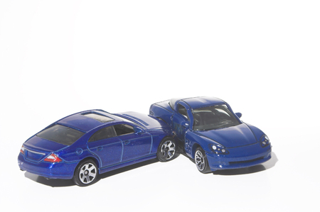 involving: A car wreck involving two miniature toy cars. Stock Photo