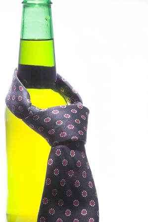 A necktie draped around an ice cold beer.