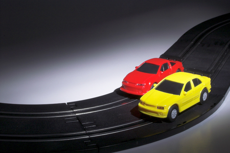 Two slot cars racing on a track at night.
