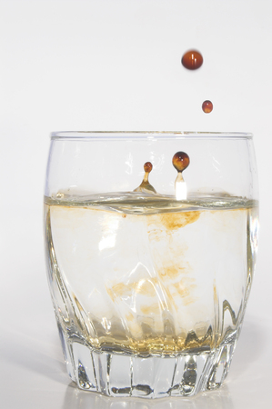 dirty water: Oil drops polluting clean water in a drinking glass. Stock Photo