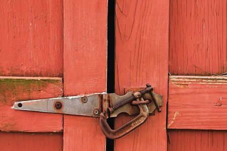 A red barn door with a c-clamp lock. Stock Photo - 1613801