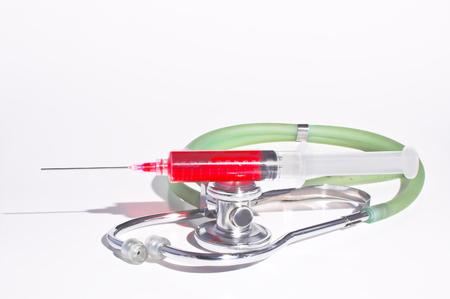 hypodermic syringe: A professional medical stethoscope and a hypodermic syringe.