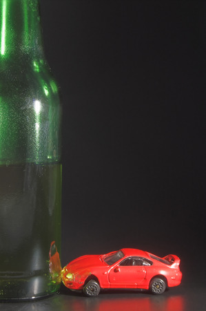 A drunk driver crashes his car into a giant beer bottle. photo