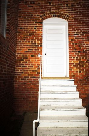 The brightly lit back door of an old church.