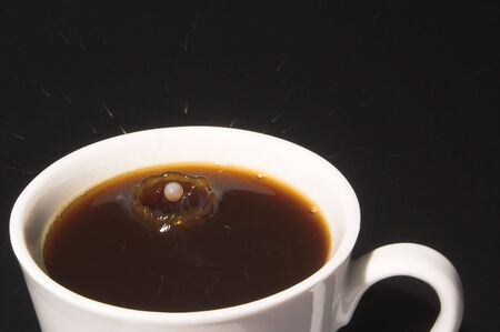 Drop of milk splashing into a cup of coffee.