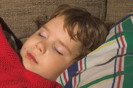 end of a long day: A young boy, with a dirty face, sleeping Stock Photo
