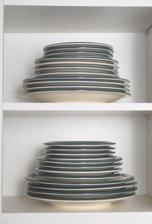 armario cocina: Pilas de platos en un armario de cocina. Foto de archivo