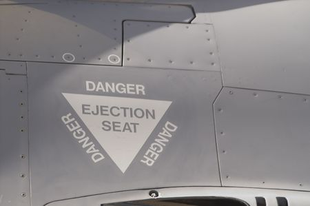 ejector: The ejection seat warning label on a fighter jet.