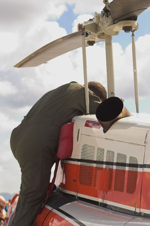 A specialized mechanic working on a US Coast Guard helicopter.