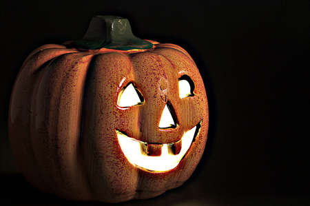 ghostly: A lighted jack-o-lantern on a dark halloween night.