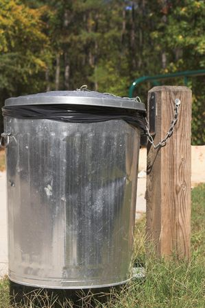 A silver trash can attached to a post. Imagens