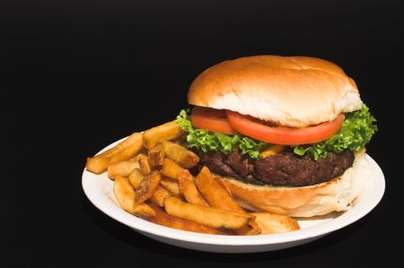 all american burger: A delicious cheeseburger and an order of French fries.