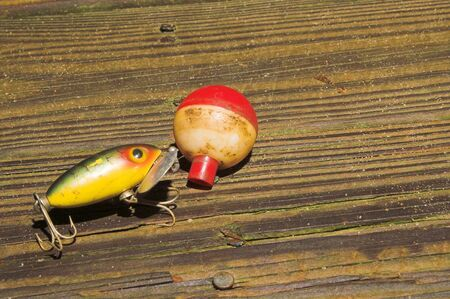 jitter: An old fishing lure and bobber sitting on a pier.