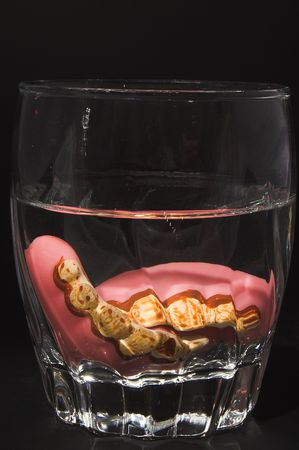 A set of stained false teeth in a cleaning solution. photo