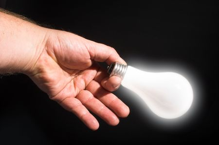 A person powering a light bulb by holding it. Stock Photo - 2017515