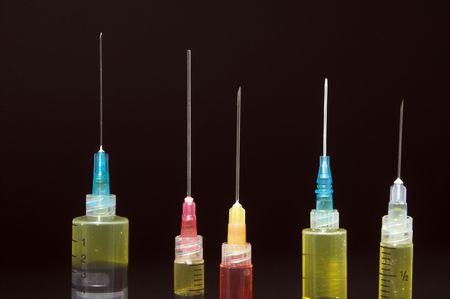 inject: A set of sharp medical pharmaceutical syringes.