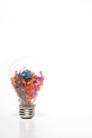 A light bulb filled with paper confetti. Stock Photo - 2094981