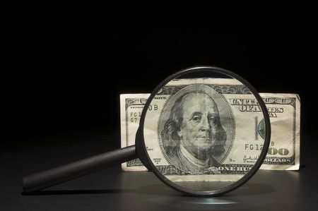 A 100 dollar bill under a magnifying glass. photo