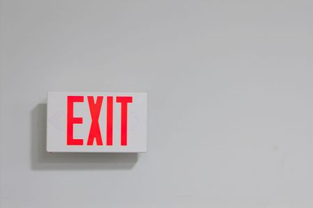 An exit sign on a wall marking the way out. Banco de Imagens