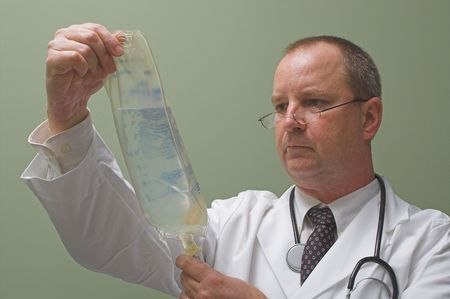 A medical doctor preparing an IV solution. photo
