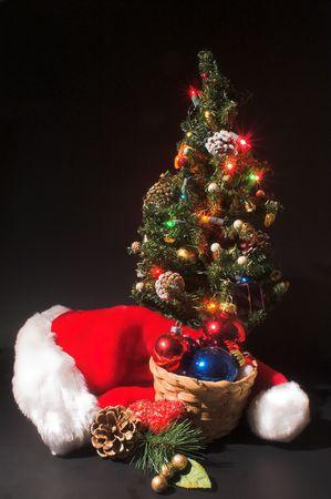 Christmas Scene - Santa hat, a Christmas tree and a basket of ornaments. photo