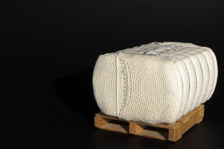 cotton crop: A bale of raw cotton on a pallet. Stock Photo