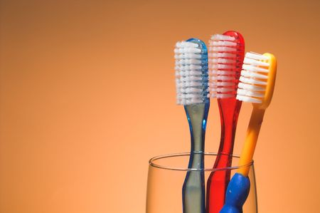gingivitis: A familys toothbrushes in a glass container.