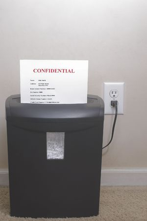 confidentiality: A shredder with confidential information - Identity theft concept.