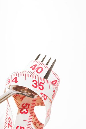 eat right: Weight Loss Concept - A tailors tape on a fork. Stock Photo