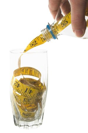 newyears: Weight Loss Concept - A tailors tape pouring into a drinking glass.