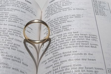 A wedding ring on a bible open to marriage scripture. photo