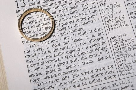 A wedding ring on a bible open to marriage scripture.
