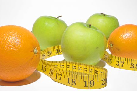 eat right: A tailors tape snaking through apples and oranges.