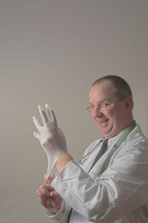 A goofy doctor putting on a rubber surgical glove. Stock Photo - 2298360