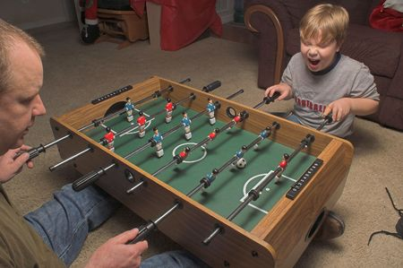 A man and a boy playing a game of foosball. photo