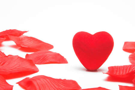A lone heart in the middle of artificial rose petals. Stock Photo - 2361107
