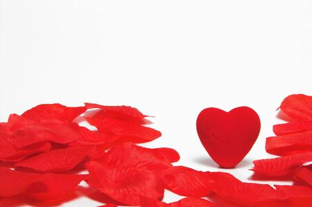 amore: A lone heart in the middle of artificial rose petals. Stock Photo