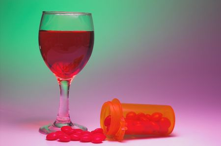 A glass of wine and a bottle of pills.